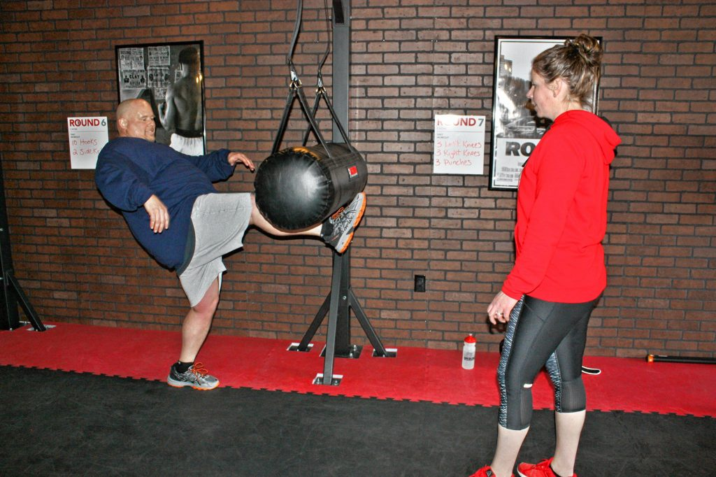9Round owner Laurie Weingartner works with Les Reed on a kicking workout at 9Round, the new kickboxing-style gym on Ford Eddy Road, last week. JON BODELL / Insider staff