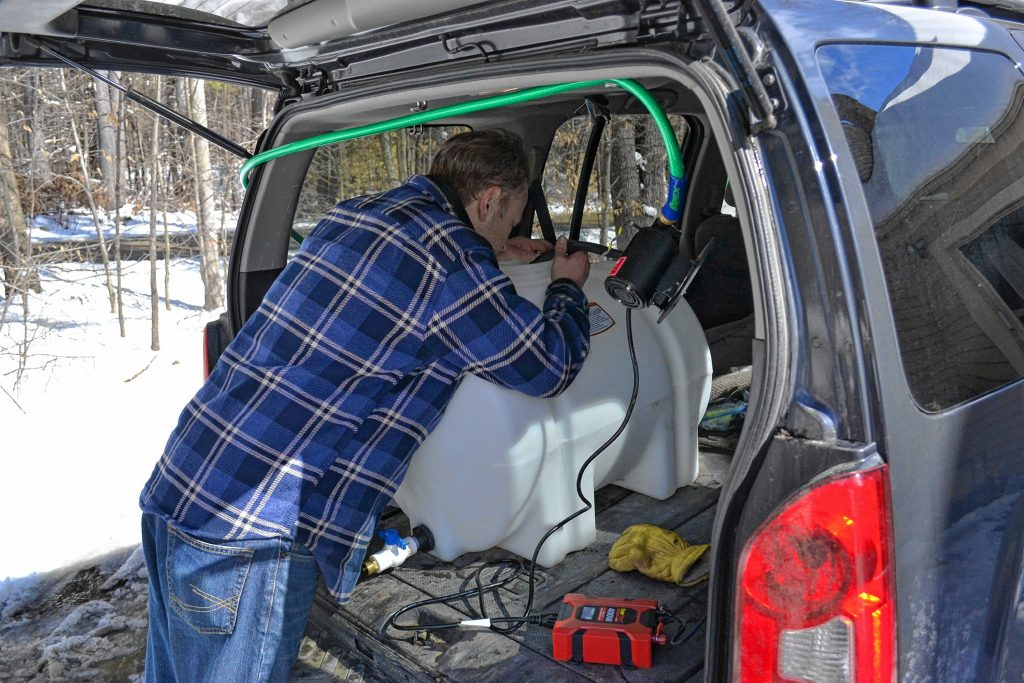 Andrew Mattiace hooks up a pump to the sap holding tank in his vehicle to transfer his sap to another holding container that will feed his evaporator. TIM GOODWIN / Insider staff