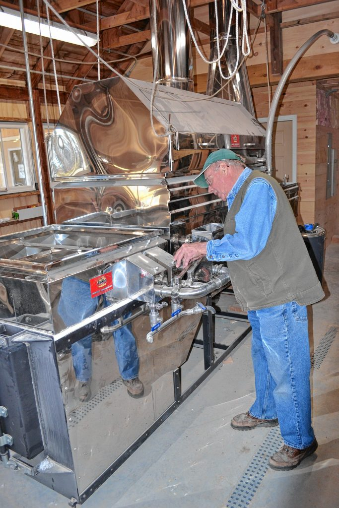 Mapletree Farm owner Dean Wilber installs a thermometer in the new evaporator that is the star of the show in his newly expanded sugarhouse. TIM GOODWIN / Insider staff