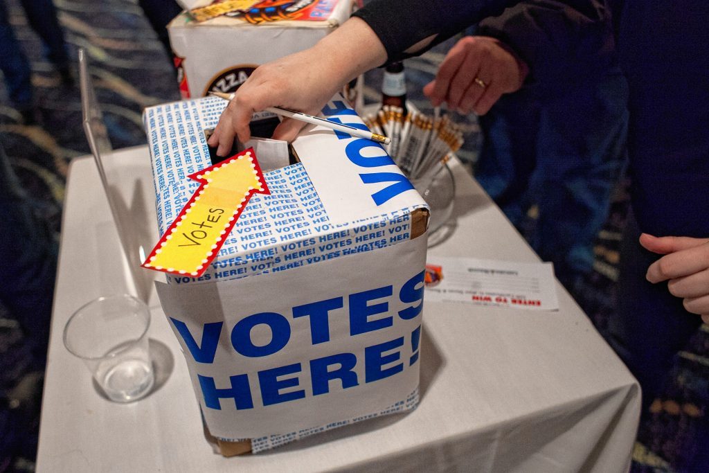 People place ballots into the voting box during the Pizza Pie Showdown at the Holiday Inn in downtown Concord on Pi Day, Mar. 14, 2018. Proceeds from the event, hosted by the Concord Monitor and Insider, went to support the Friendly Kitchen. (ELIZABETH FRANTZ / Monitor staff) Elizabeth Frantz