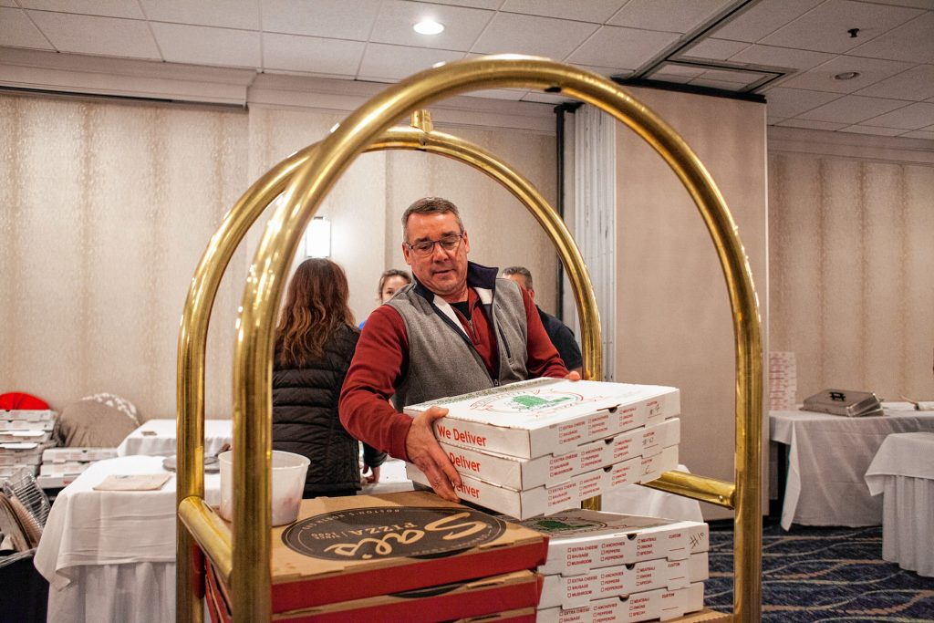 Friendly Kitchen coordinator Troy Burke gathers donated pizzas at the end of the Pizza Pie Showdown at the Holiday Inn in downtown Concord on Pi Day, Mar. 14, 2018. Proceeds from the event, hosted by the Concord Monitor and Insider, went to support the Friendly Kitchen. (ELIZABETH FRANTZ / Monitor staff) Elizabeth Frantz