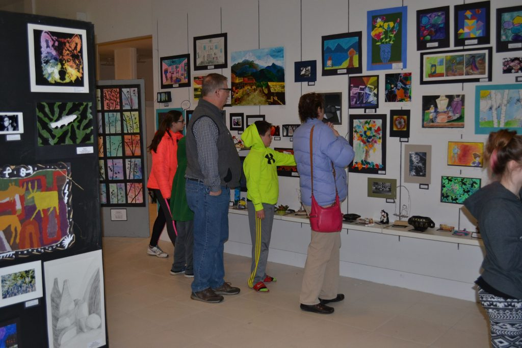 A group of art enthusiasts peruse the Concord School District Youth Art Month show during last week's opening. Tim Goodwin