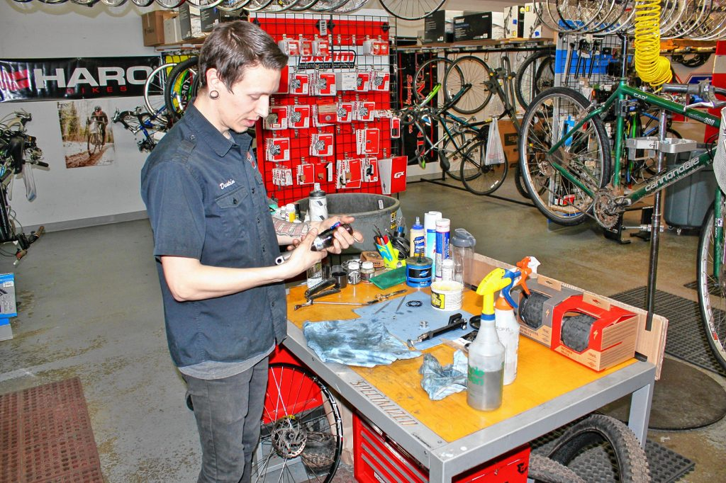 Dustin Iverson (no relation to Allen) performs some maintenance on one of the rear shocks of a high-end, full-suspension bike at Goodale's Bike Shop last week. Jobs like this are pretty common at the shop at this time of year, he said. JON BODELL / Insider staff
