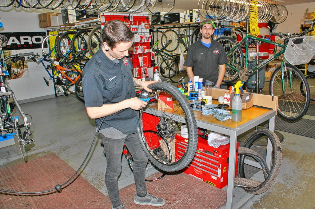 Dustin Iverson inflates a tire at Goodale's Bike Shop last week.  If your bike has been sitting in the garage (or worse, outside) for the past six months or so, you'll want to make sure first and foremost that you have air in your tires -- it makes riding a lot more fun. JON BODELL / Insider staff