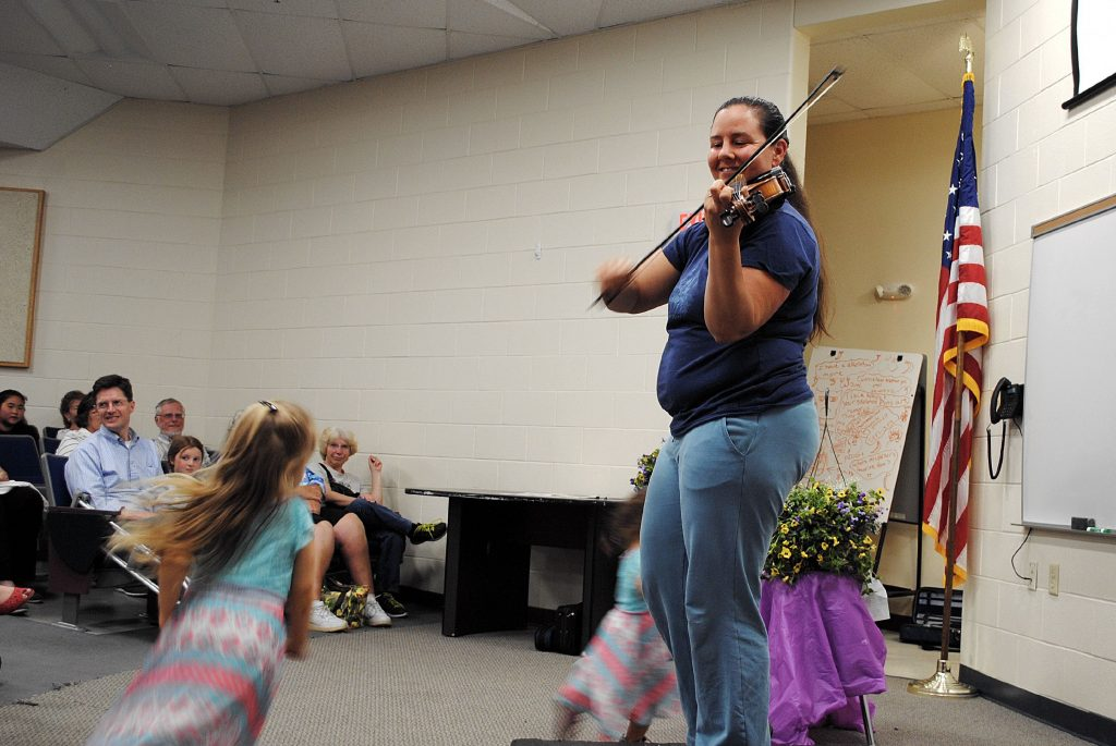 Heather Mike Morris, the former executive director of the Pittsfield Youth Workshop, plays the fiddle Friday, while her girls dance in circles around her in the lecture hall of Pittsfield Middle High School. NICK REID