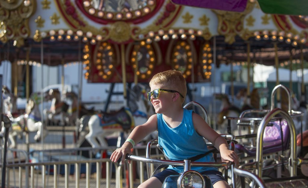 Ryker Comeau, 5, of Concord smiles at his parents while on the motorcycle ride at the Kiwanis Spring Fair on Thursday, May 18, 2017. GEOFF FORESTER