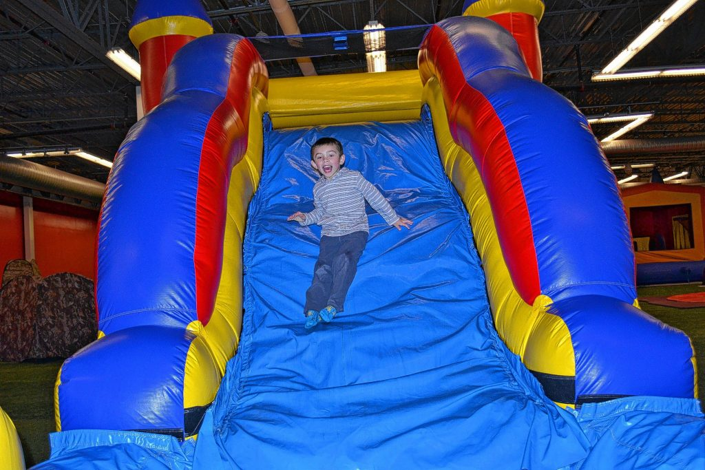 Chris Smykil belly-flops onto Jon White in the Sumo wrestling ring inside Bounce House Entertainment Center. Good thing they were wearing those suits! Below: Braden Bosco, 5, has a whale of a time.