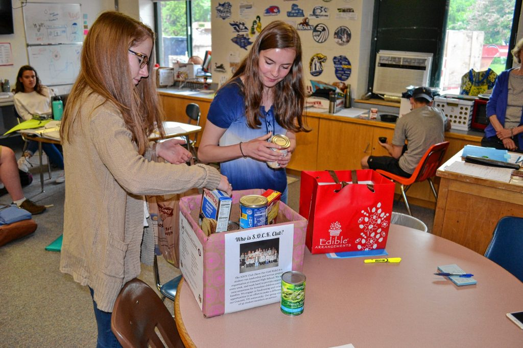 Mckenna Anderson and Cait McAllister, president and vice president of the Concord High SOCK Club, put non-perishable items in one of the collection boxes for the club's newly created Crimson Care Closet. TIM GOODWIN / Insider staff