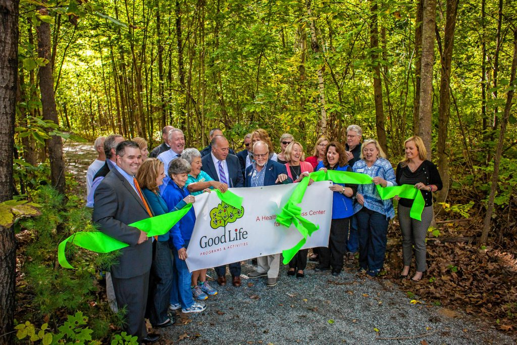 Mayor Jim Bouley makes the cut during the ribbon cutting ceremony at Smokestack Center in Concord on Oct. 6, 2016. Owners of Smokestack and their tenants, such as GoodLife Programs & Activities, hope the short trail is only the start of a larger vision for the wooded area off the center's parking lot. (ELIZABETH FRANTZ / Monitor staff) ELIZABETH FRANTZ