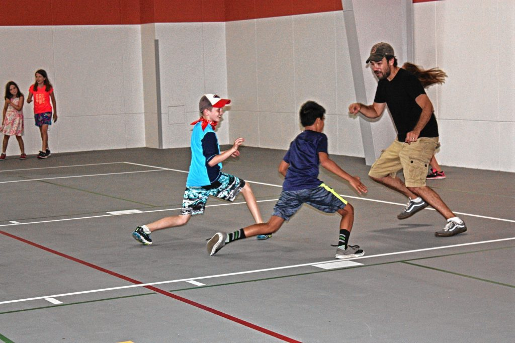 Jon gets schooled in a game of everybody's it tag with campers at the new City Wide Community Center last week. Who knew little kids could be so fast and nimble? OLIVIA HARDING / For the Insider