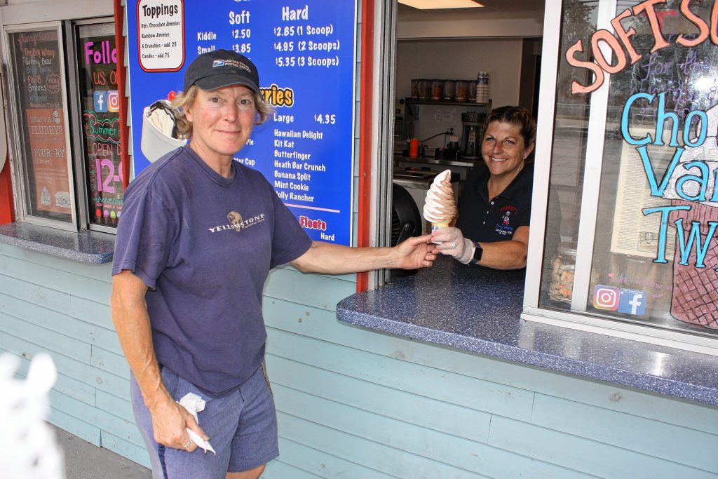 Carol Frekey-Harkness, owner of Frekey's Dairy Freeze, serves a soft-serve cone to Chris Buckley on an overcast Wednesday last week.  JON BODELL / Insider staff