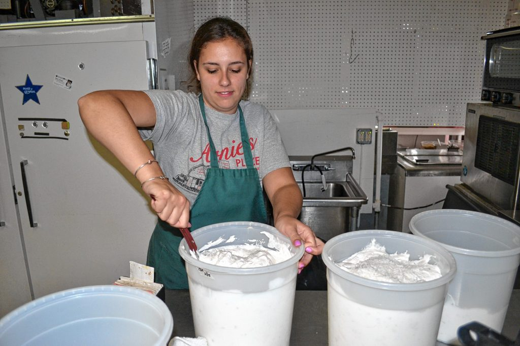 Hannah Thompson adds some shredded coconut to a batch of coconut roasted almond at Arnie's Place. TIM GOODWIN / Insider staff