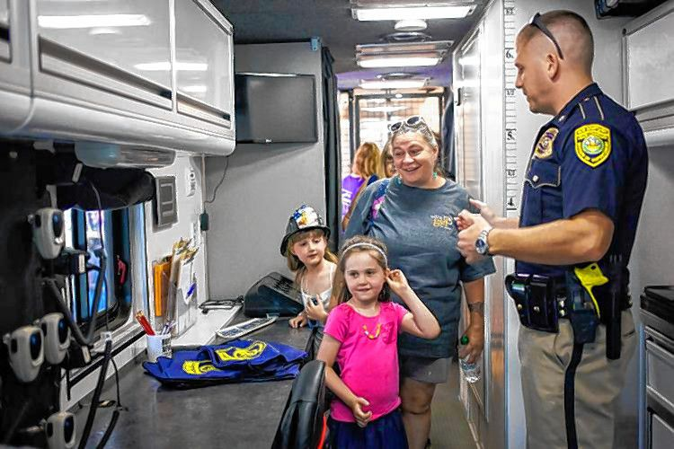 Becky Russell (center) of Concord and 6-year-old Molly McGregor (front) learn about the DUI Mobile Command Center from State Division of Liquor Enforcement investigator Glen Bullock during National Night Out at Rollins Park in Concord on Aug. 1, 2017. ELIZABETH FRANTZ / Monitor staff