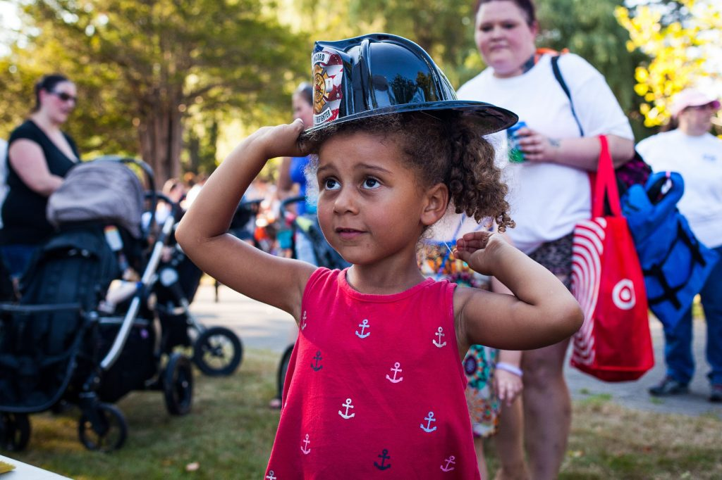 Lily Sage, 4, of Concord tries on her Concord fire department toy helmet during National Night Out at Rollins Park in Concord on Tuesday, August 1, 2017. (ELIZABETH FRANTZ / Monitor staff) ELIZABETH FRANTZ