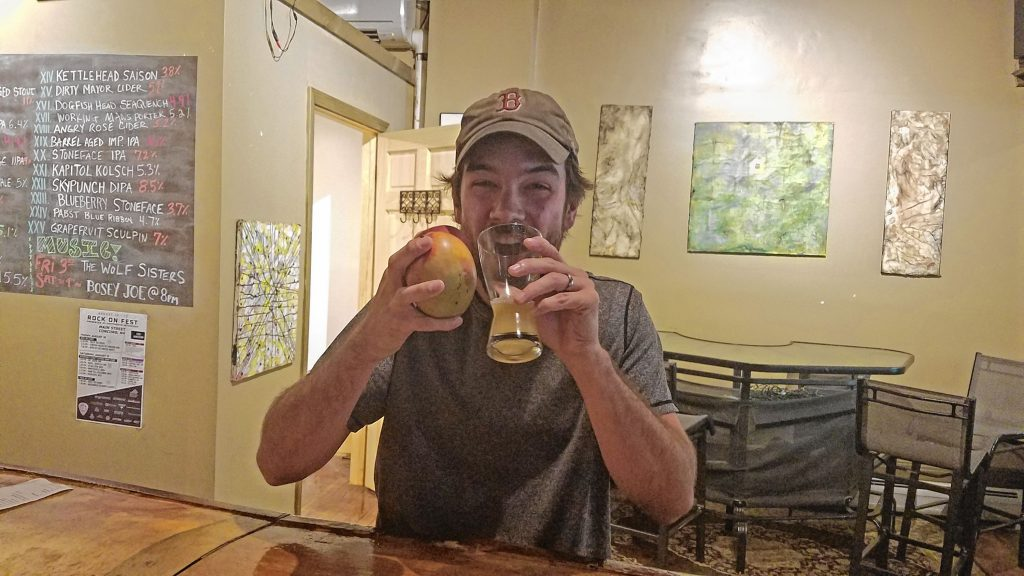 Jon attempts to drink Concord Craft Brewing Co.'s Safe Space New England IPA while also eating a mango and a peach at True Brew Barista last week. He failed miserably, but it was a fun time trying. JILL FELLBAUM / For the Insider