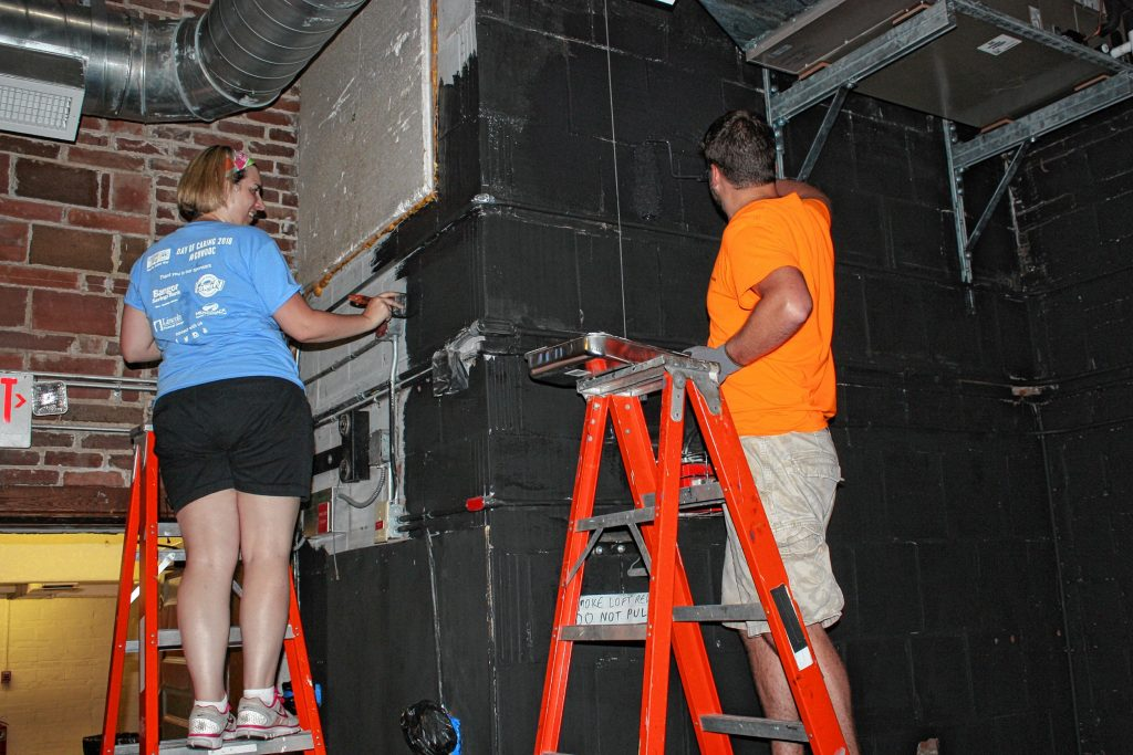 Stacey Allen with HealthTrust and Jeff Dennis, the fiance of someone who works at HealthTrust, work on painting the back wall behind the stage at the Capitol Center for the Arts as part of Granite United Way's Day of Caring on Wednesday. JON BODELL / Insider staff