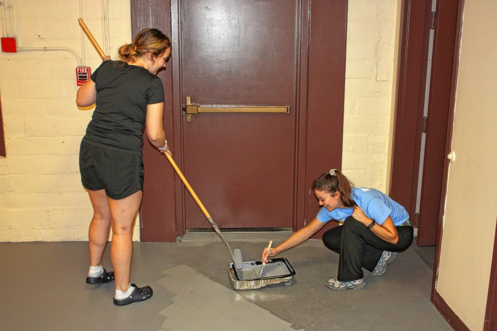 Madyn Kenney (left) with NHTI's PTK academic excellence committee and Hayleigh Yates with the Richards Group work to paint the floor backstage at the Capitol Center for the Arts on Wednesday as part of Granite United Way's Day of Caring.  JON BODELL / Insider staff