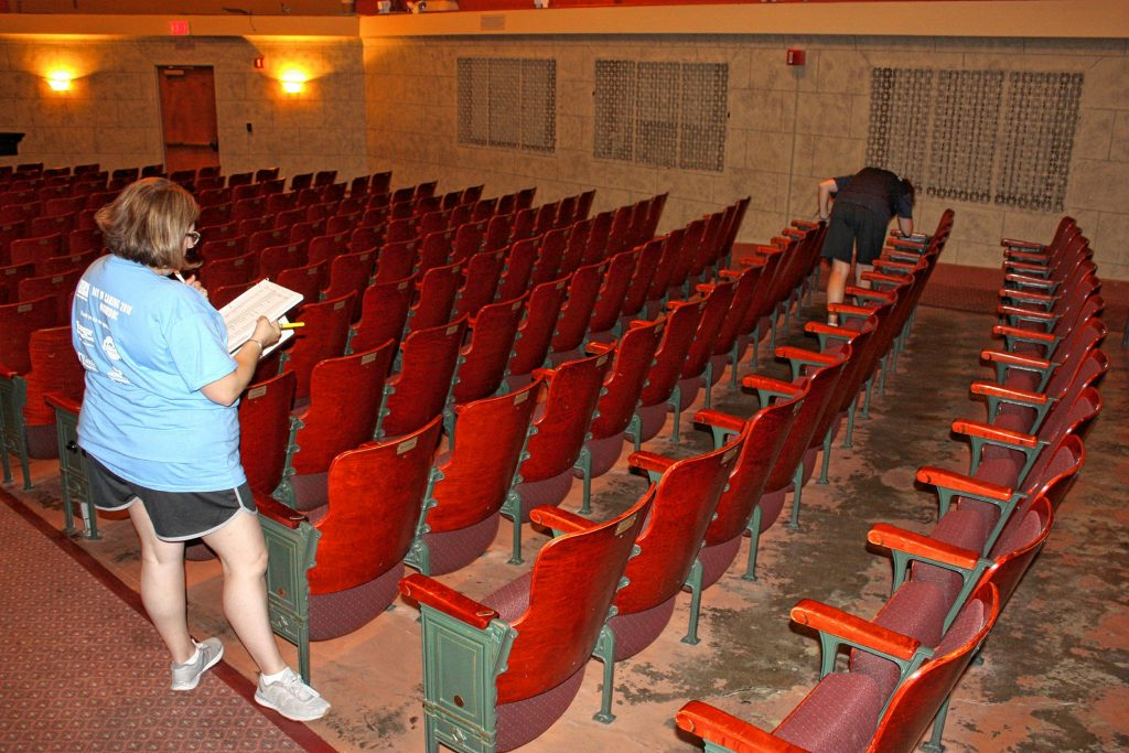 Jennifer Thompson (left) and Dianne Bird, both with HealthTrust, inspect seats at the Capitol Center for the Arts for missing number plates last Wednesday as part of Granite United Way's Day of Caring. JON BODELL / Insider staff