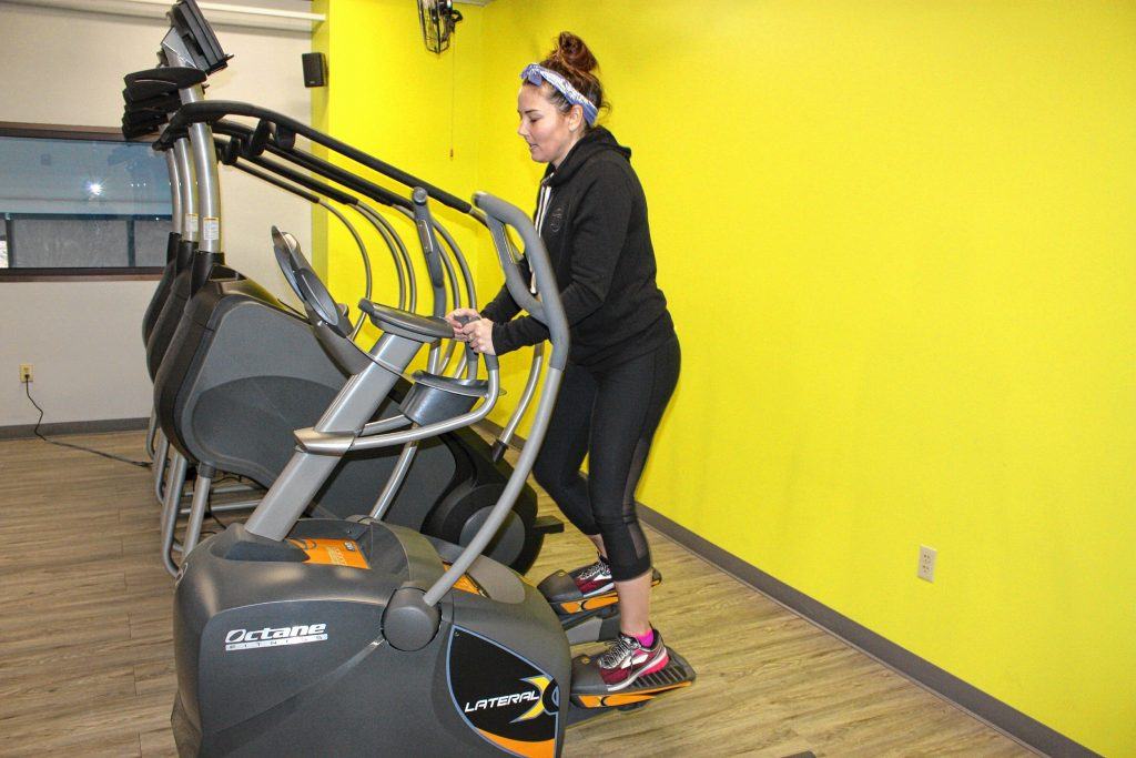 Crystal Reynolds, one of the owners of 43 Degrees North Athletic Club, demonstrates how to use a piece of exercise equipment at the fitness center last week.  JON BODELL / Insider staff