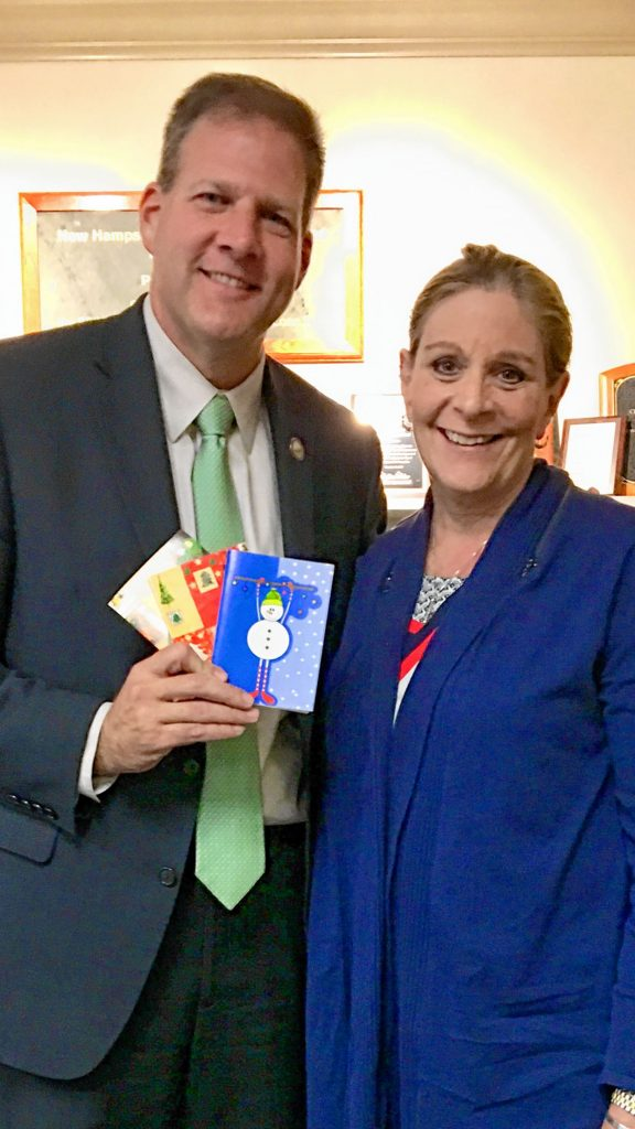 Gov. Chris Sununu holds some cards alongside Laura Landerman-Garber, who started the Holiday Cards 4 Our Military initiative, in which people from all over the Granite State -- including the governor -- wrote holiday cards to send to members of our armed forces. Courtesy of Laura Landerman-Garber