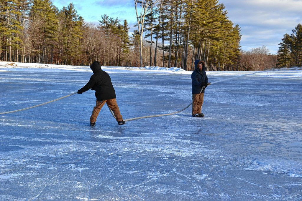 Left: The pond spraying crew taps into a city water line at Beaver Meadow and uses seven, 50-foot hoses to water the ice. Above: Justin Wheeler pulls the lengthy hose, while Lanman sprays the pond.