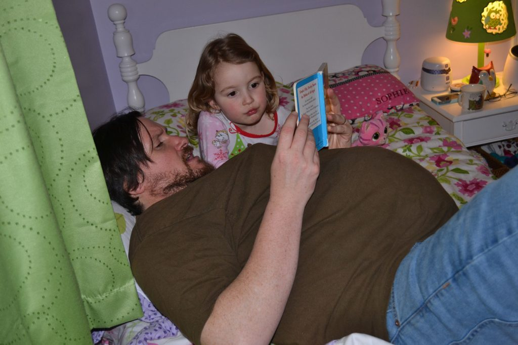 Even after a full 13 hours of being fake pregnant, Tim still found the energy to lay around and read stories to his daughter, Sophie. MARY GOODWIN / For the Insider