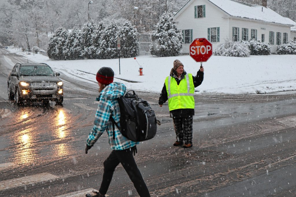 Crossing guard Rose Baker, 58, helps a student cross Warren Street on Tuesday.