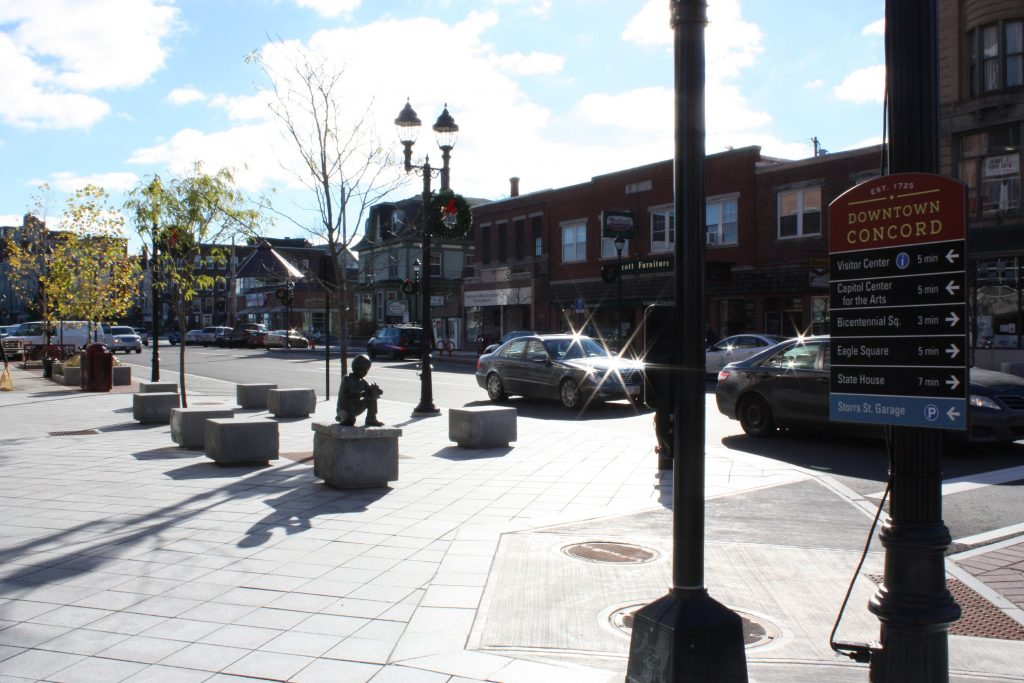 There's an absolute slew of new South Main Street stuff in this photo.  In the foreground there's a new direction-giving sign and a new light post. Behind those are new granite blocks for seating and a new statue of a boy holding a turtle, with new trees and a new trash barrel behind  them. JON BODELL / Insider staff