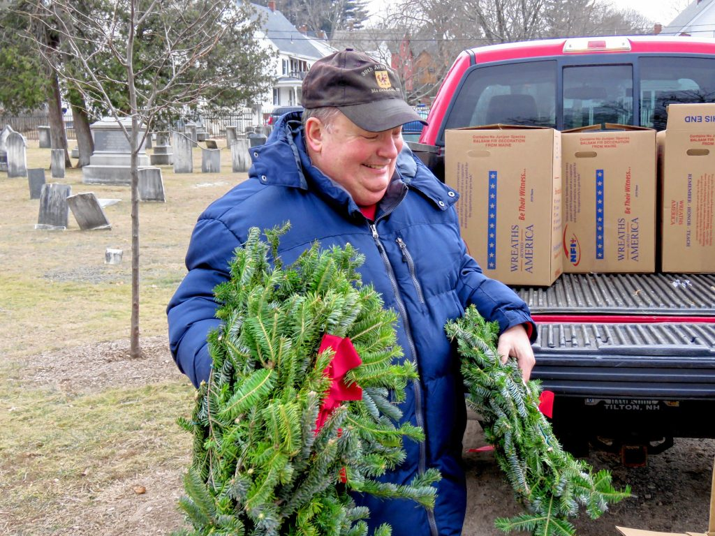 Pierce Brigade member Tom Fisk gathers up wreaths to put on veterans' graves in the Old North Cemetery in Concord on Friday. Caitlin Andrews