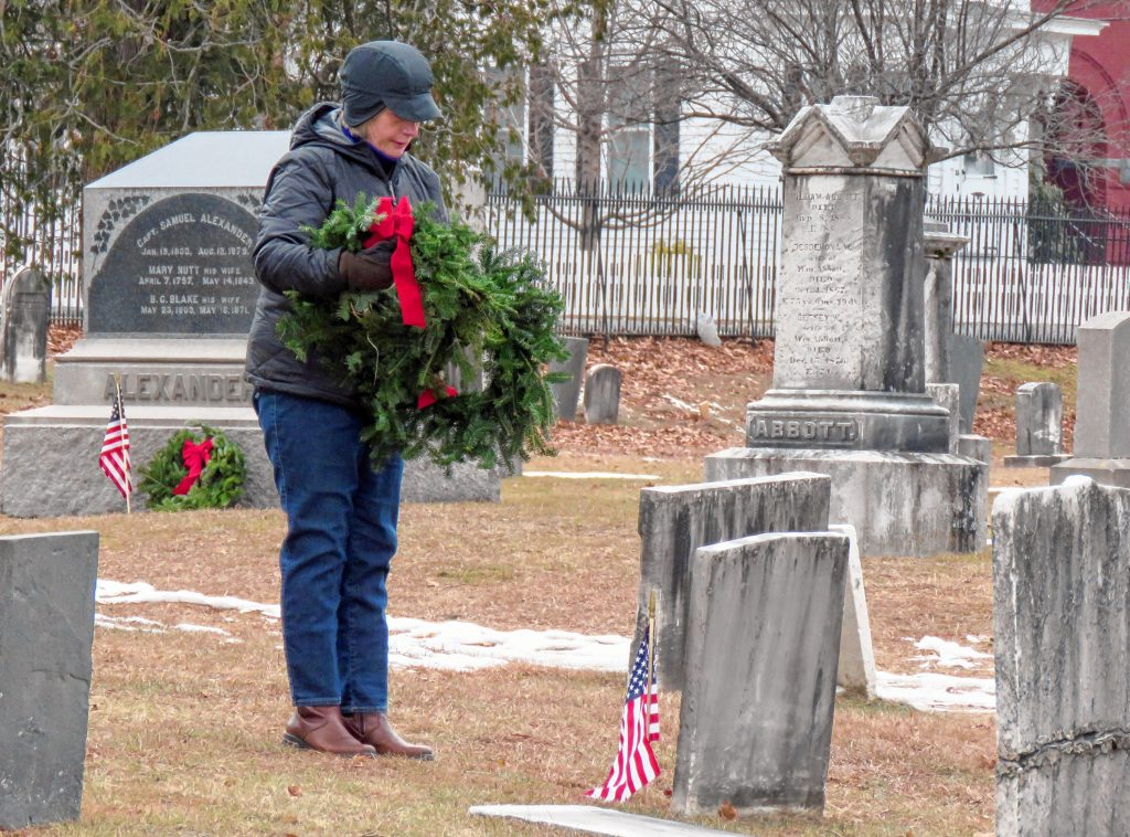 Pierce Brigade member Ginny Friburg lays a wreath on a veteran's grave in the Old North Cemetery in Concord on Friday. Caitlin Andrews