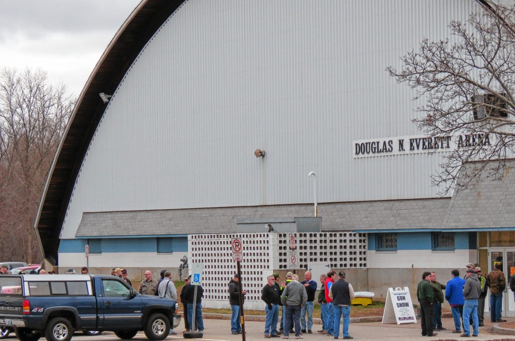 A line of people wait outside the Douglas N. Everett Arena to get into an event.