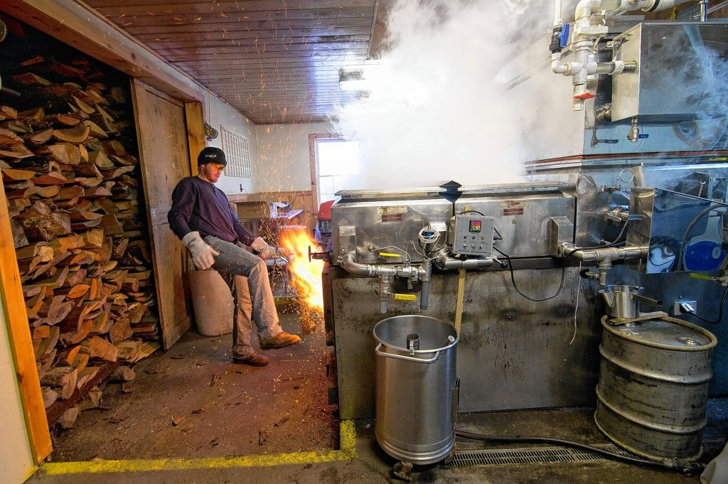 Jeff Moore of Windswept Maple Farm in Loudon uses his foot to close the door of the wood-fired evaporator at their maple processing building. It was warm enough this week to make syrup.  (GEOFF FORESTER / Monitor staff)