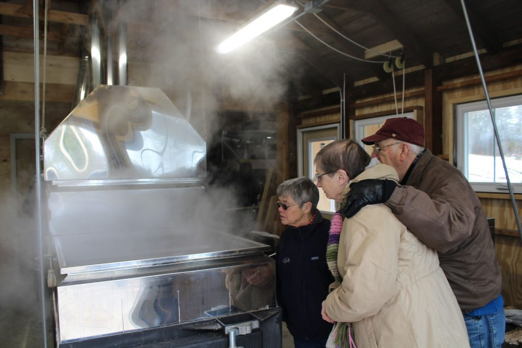 Linda Lynch, and Leo and Gloria Van Beaver watch sap collected at Havenwood boiled into syrup at Mapletree Farm. Courtesy