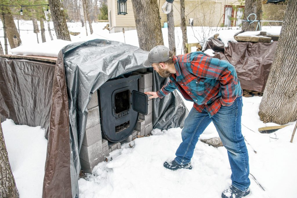 Andrew Mattiace opens up the converted oil tank he created for the burner of his evaportation process for sap in the back of his Bow home on Saturday, March 2, 2019. GEOFF FORESTER