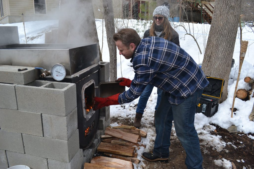 Andrew Mattiace tends to the fire while boiling his fourth batch of maple syrup on Saturday, while his girlfriend Wendy Zona looks on. TIM GOODWIN / Insider staff