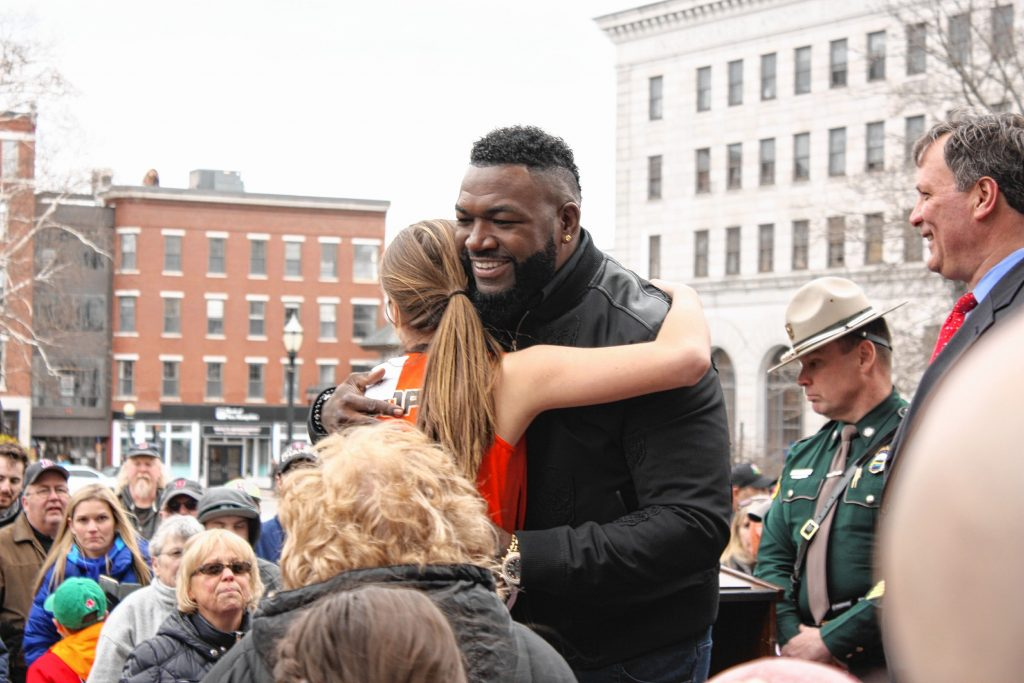 David Ortiz hugs a Keene youth softball player during a launch event for a new Red Sox scratch ticket at the State House last Wednesday.  JON BODELL / Insider staff