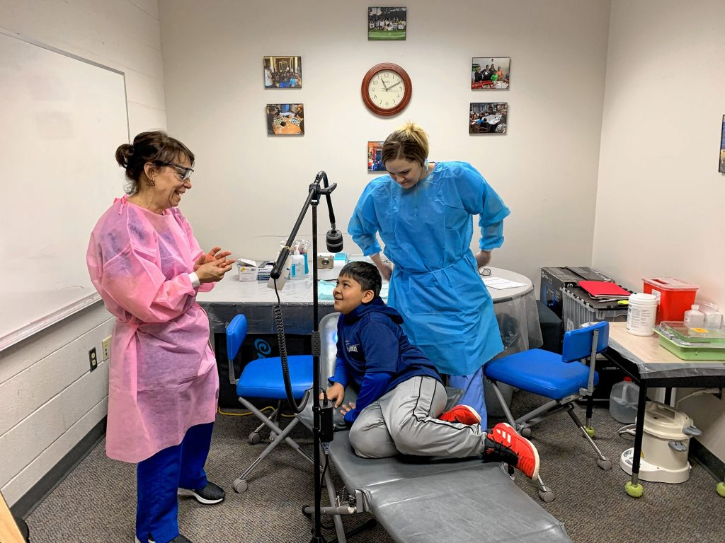 Above: Certified Public Health Hygienist Mary Davis (left) and Dental Assistant Brittani Oldham comfort second-grader Anurag Das before he receives dental treatment last Wednesday at Penacook Elementary School. Below: Brady Humphreys gets some work done too.