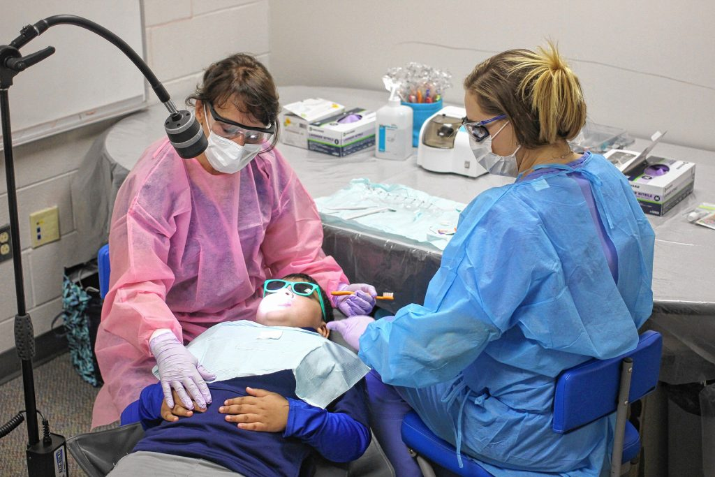 Certified Public Health Hygienist Mary Davis (left) and Dental Assistant Brittani Oldham (right) provide dental care to second grader Anurag Das (center) at Penacook Elementary School Wednesday.