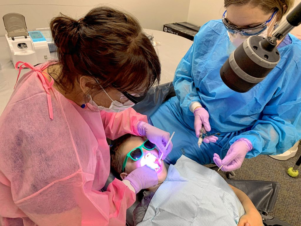 Certified Public Health Hygienist Mary Davis (left) and Dental Assistant Brittani Oldham (right) provide dental care to second grader Brady Humphreys (center) at Penacook Elementary School Wednesday.