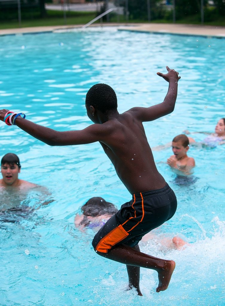 Jean Pierre Nzeyimana, 10, jumps in the Kimball pool on North State Street Monday only to find for himself that other had: the water was really cold.  (GEOFF FORESTER / Monitor staff) GEOFF FORESTER