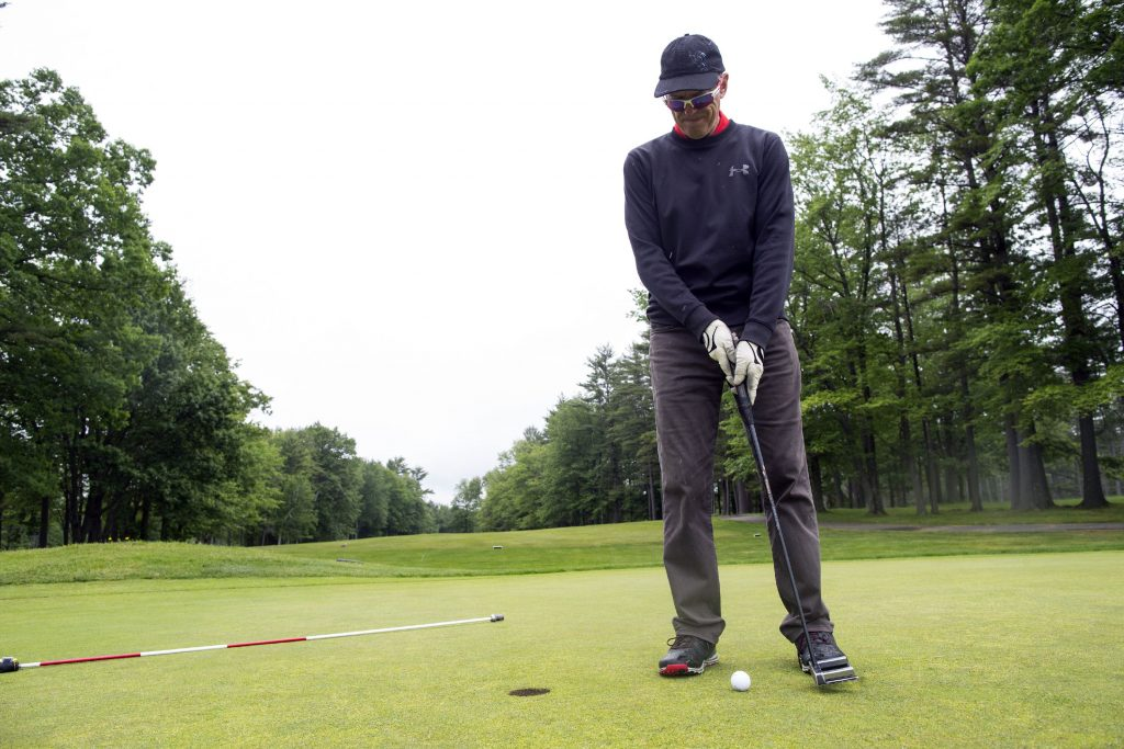 Ed Thompson of Bow taps in on the 9th hole of the Beaver Meadow Golf Course on Tuesday, May 5, 2018. Thompson played in spite of the rain. GEOFF FORESTER