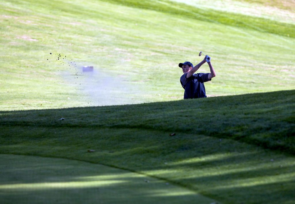 Bow's Ronan Lucey blasts out of a trap near the green on the fourth hole at Canterbury Woods Thursday afternoon. Lucey went on to birdie the hole after leaving the shot three feet from the hole. GEOFF FORESTER