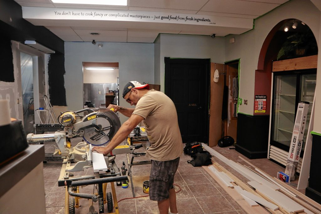 Cherry Blossom Renovation employee Dana Haynes works on site of The Crust and Crumb Baking Co. expansion project on Friday. The Crust and Crumb Baking Co. is expanding into the space previously occupied by  Wellington's Marketplace.