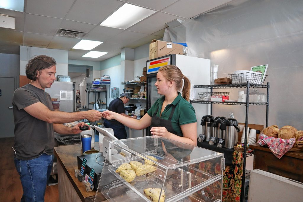 Steve Troppoli checks out with employee Jenna Meyer at The Crust and Crumb Baking Co. in Concord last Thursday.