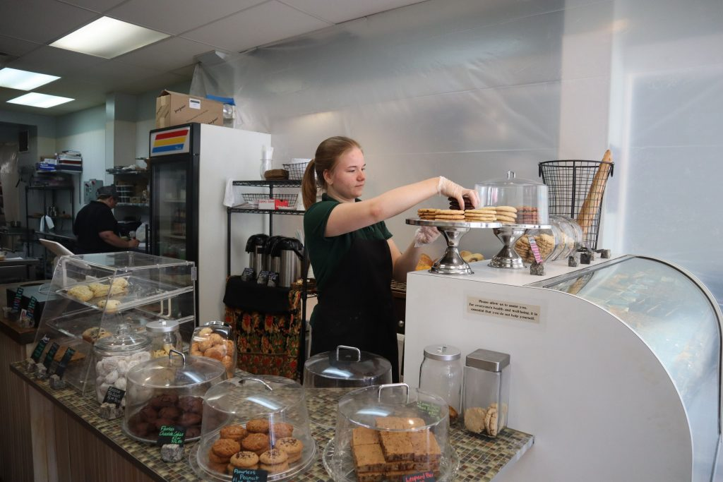 With the walls now replaced by protective plastic during renovations, Crust and Crumb Baking Co. employee Jenna Meyer works behind the shop's counter on Thursday. The business will add new items to its menu and will hire additional staff.
