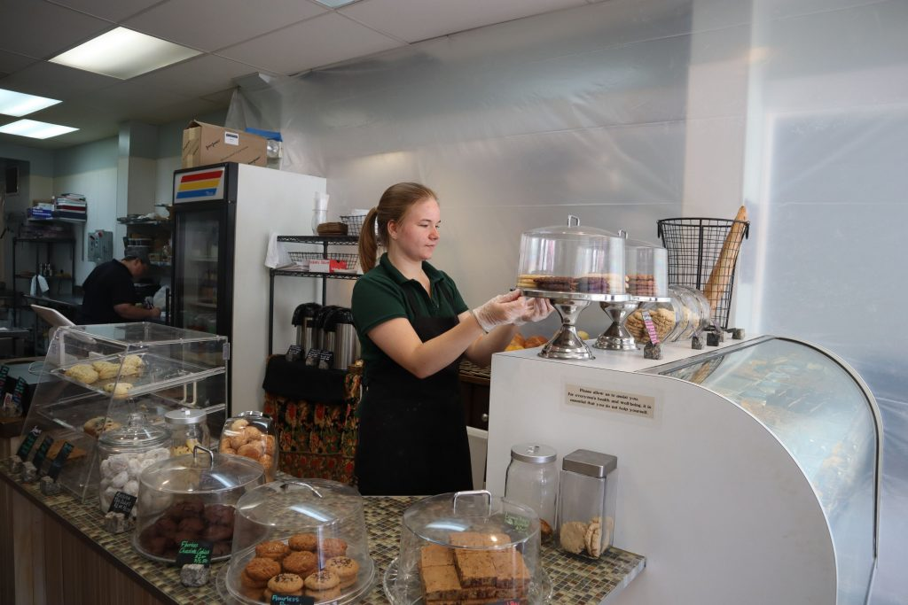 The Crust and Crumb Baking Co. employee Jenna Meyer works behind the shop's counter on Thursday.
