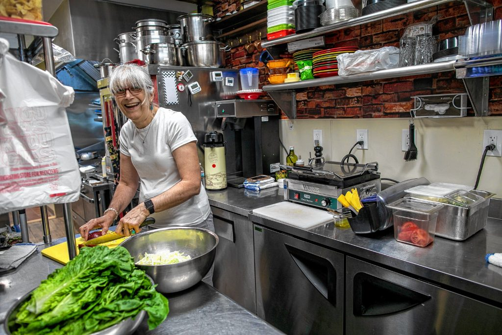 Nina Mujakobic, owner of Nina's Bistor and Sandwiches, cuts up some cabbage in the kitchen of the eatery that has replaced the The Sandwich Depot on Hall Street in Concord. GEOFF FORESTER