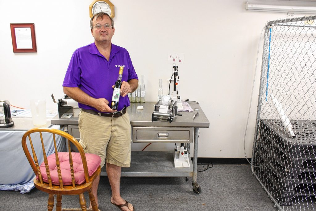 Black Cove Beverages owner Frank Marino shows a bottle of his Morecello at his facility in Meredith. JON BODELL / Insider staff