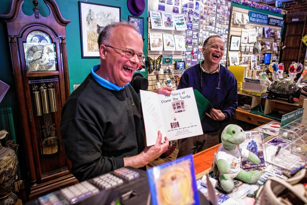 Jim Tonner (left), who co-owns TwinDesigns Gift Shop with his twin brother Brad Tonner (right), show the book they produced to customers on Monday, June 25, 2018.