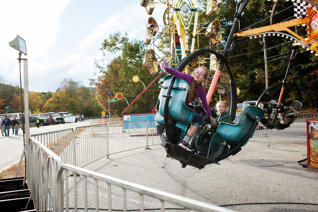 Sophia Harne, 13, of Warner waves as she spots a group of her friends while riding the Tornado ride in the Midway with her friend Cierra Mailloux, 14, of Hopkinton at the Warner Fall Foliage Festival on Saturday, Oct. 11, 2014.  (JULIE BYRD-JENKINS / Monitor staff) JULIE BYRD-JENKINS